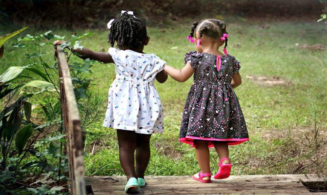 Due bambine di spalle che si tengono per mano
