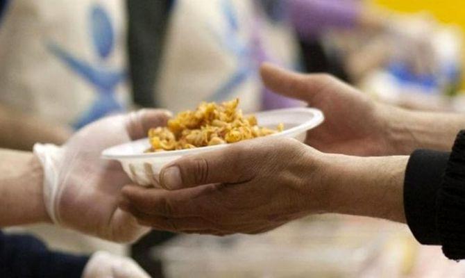 Una persona porge un piatto di pasta a un'altra