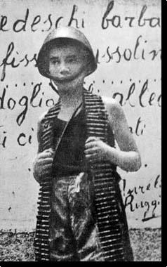 un ragazzino con un casco dell'esercito e con indosso una cartucciera