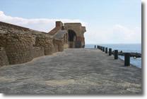 pontile del castello con muretto basso sulla sinistra e circondato dal mare