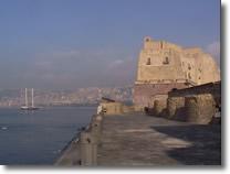 castel dell'ovo visto dal pontile. In lontananza è visibile parte del panorama della città di napoli ed una barca a vela in mezzo al mare