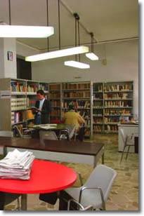ampio salone con librerie, sedie, scrivanie e persone che leggono