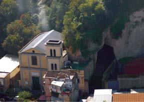 foto dall'alto di una chiesa acostata ad una parete rocciosa con a lato l'ingresso ad una grande cavità
