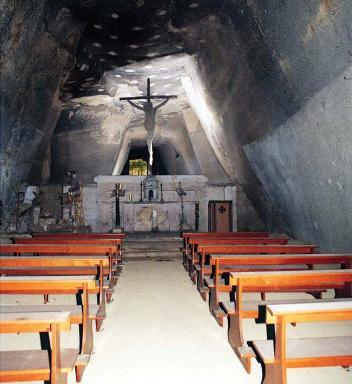 interno di un'antica chiesa con crocifisso al di sopra di un altare ed una serie di panche