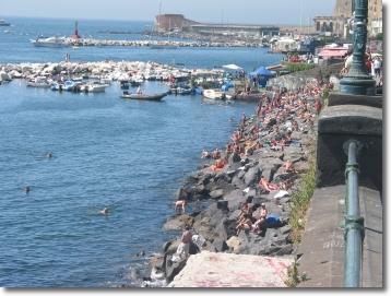 bagnanti sugli scogli del lungomare di Napoli