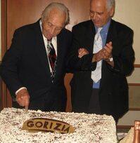 Foto di due uomini anziani che tagliano una torta